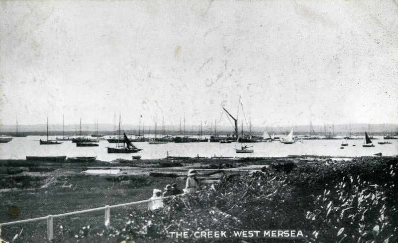 The Creek, West Mersea - a post card view along Coast Road. The barge dressed overall and a line of boats suggest it is Regatta Day.