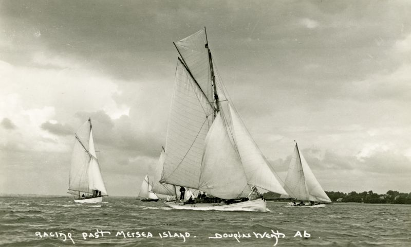 Racing past Mersea Island. Postcard by Douglas Went. West Mersea Yacht Club Regatta cJuly 1932. The yacht on the left is thought to be WINDFLOWER, built Emsworth 1928, Official No 149150. Owned by Col. Cuthbert Buckle of London EC4. The yacht in the centre is thought to be PETRONA.
