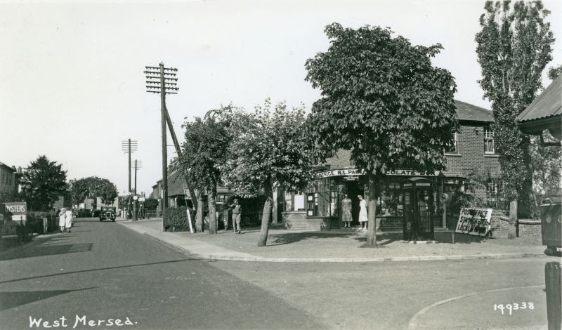 West Mersea. High Street and Post Office Corner. The Post Office is run by R.L. Page, also titled Chocolate Box. Telephone box outside. There are still petrol pumps outside the bus station. Postcard 149338.