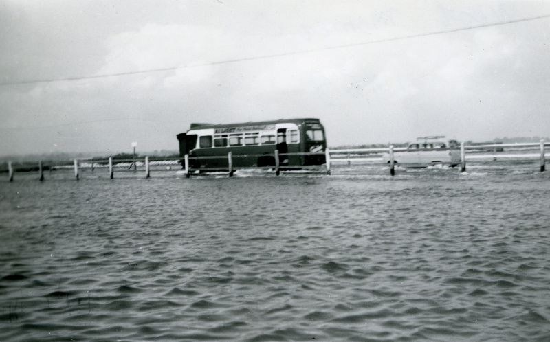 Eastern National bus going through the water at the Strood, in the days when bus services were not curtailed by the high tide. Ford Anglia Estate behind it ? 