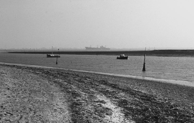 Besom Creek at the western end of Mersea Island with the River Blackwater beyond. The vessel laid up in the river is thought to be WILD AUK, 9,601 tons gross, built 1971. She was sold and renamed OLYMPIAN REEFER in 1980, broken up at Mumbai in 1999. Date: cAugust 1975.