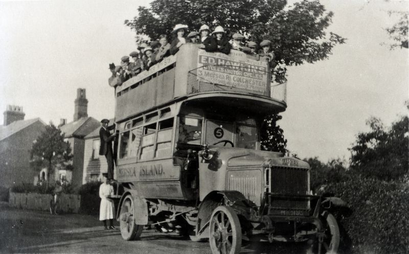 A Primrose Bus in 1920 parked in High Street near the entrance to Captains Road prior to leaving on a school trip to London Zoo. Headmaster Mr. Green with the top hat can be seen on the upper deck at the rear of the bus. Ernie Fenn on the outside of the bus is fixing the destination sign in the small window. The bus is HK5195.