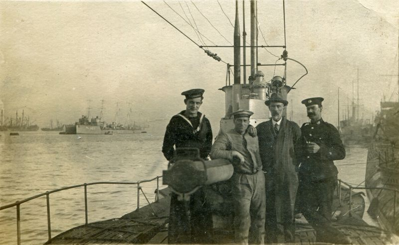 Seamen aboard a submarine, possibly a U-boat. The destroyer in the background is pennant number H65. Photograph  ...