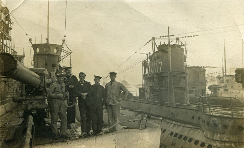 Royal Navy seamen aboard a submarine. To the right are submarines U117, UB148 and AK1.