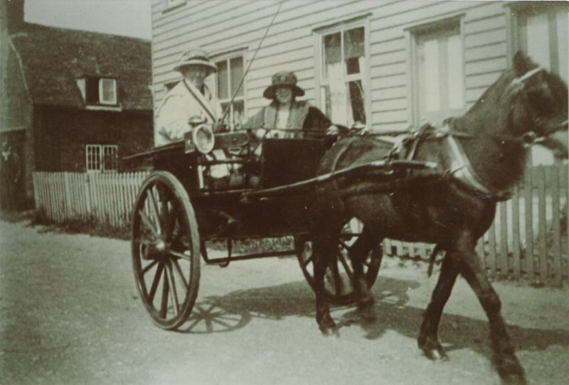 Mrs Josie Condon [ Mary Josephine Condon ] driving a pony and trap at the top of The Lane. The passenger is Mrs Rhona Keenlyside, her daughter. Josie Mary Condon lived in Vine Cottage up to about 1926. The weatherboard cottages on the right are Smithfield Cottages in Firs Chase. The pony's name was Judy.
