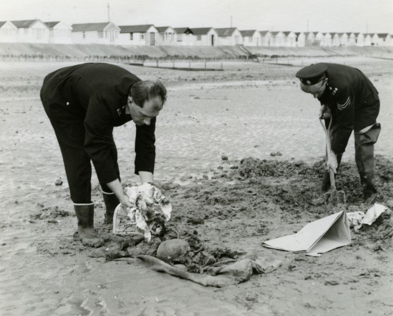 Police Sergeant Tony Butcher and Police Constable David Passfield recovering a skeleton found on the beach by Coopers Beach, East Mersea. The old chalets at Coopers Beach are inthe background. 