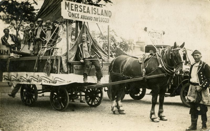 Mersea Island entry winnner in Colchester Carnival Cup competition. Once aboard the lugger. Coal cart from Clifford White & Co., driver Fred Cook. Mrs Connie Mole (now Mrs C. Clarke) next to the mast. William Wyatt is in the middle of the group on the cart. Arthur Wade on the right, standing with the horse. 