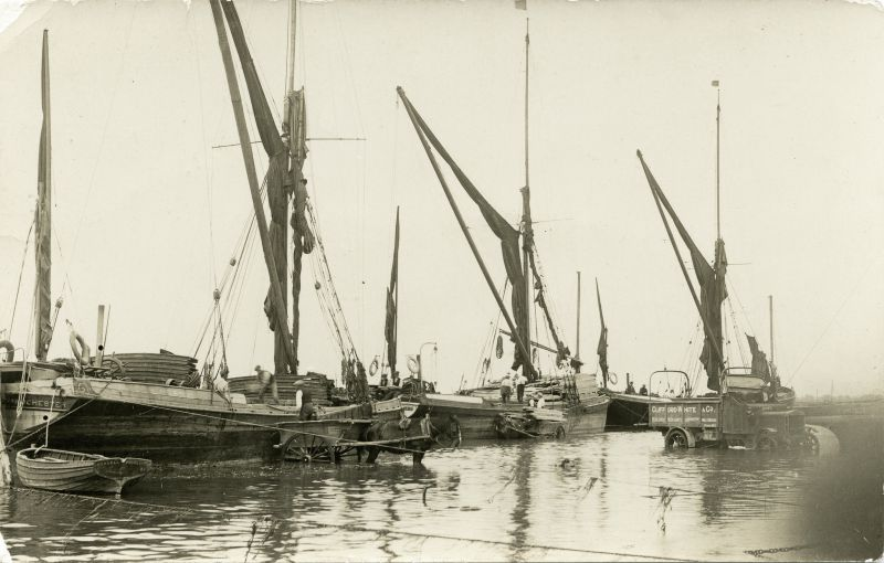 Barges unloading on West Mersea Hard. Clifford White lorry N01671. Left hand barge is RUSSELL on dinghy, with bricks. GOLDEN FLEECE in centre with timber and right hand final barge is unloading cement.
