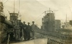 12. ID PBIB_NAV_423 Royal Navy seamen aboard a submarine. To the right are submarines U117, UB148 and AK1.